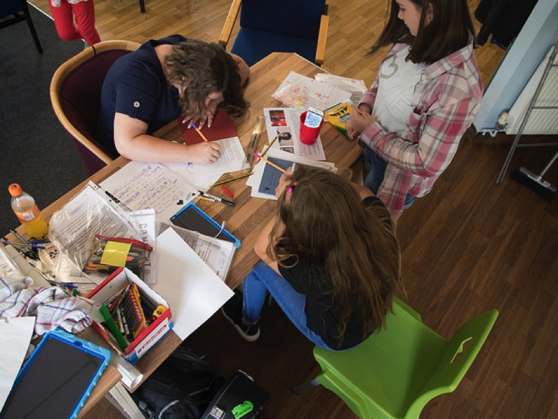 Photo of young people writing lyrics for Pedestrian's Concept project.